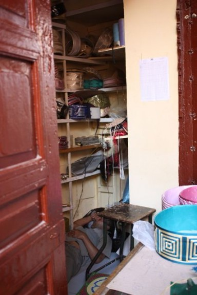 Meknes Morocco, craft booth where the man who runs is asleeps in the booth on the floor