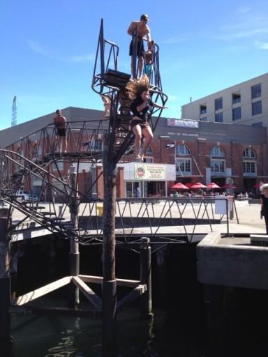 cute girl jumps form Taranaki Wharf Jump Platform