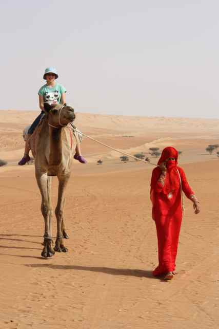 Sarah Albom riding a camel in a Bedouin Camp in the interior of Oman