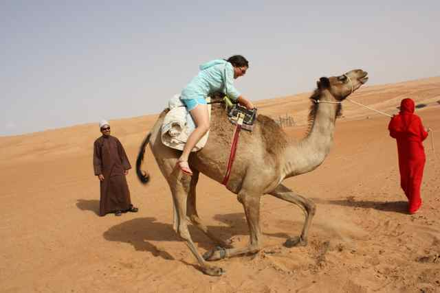 Melissa Albom getting up on a camel in a Bedouin Camp in the interior of Oman